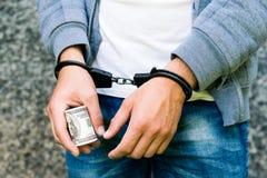 Gearresteerde gewelddadig in handcuffs met dollarbankbiljet Gearresteerd voor a royalty-vrije stock foto