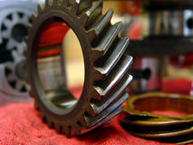 Gears. Displaying auto timing gears on a shop table with oil pump gears in the background royalty free stock photos