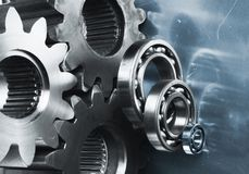 Gears against blue steel Royalty Free Stock Photos