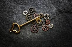 Gears and antique key. Vintage gold key and metal gears on dark textured background Stock Image