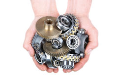 The gears and bearings. Hands hold a heap of bearings and a gears wheel on a white background royalty free stock photo