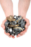 The gears and bearings. Hands hold a heap of bearings and a gears wheel on a white background stock photo