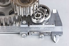 Gears and bearings with calipers. On a metal plate royalty free stock photos