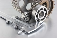 Gears and bearings with calipers. On a metal plate stock photos