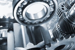 Gears and bearings, engineering. Large gearwheels and ball-bearings, blue toning idea royalty free stock photos
