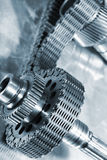 Gears and cogs powered by timing chain. Large aerospace parts, gears and cogwheels powered by timing-chain, blue toning concept stock photography