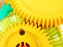 Gears and cogs system. An arrangement of two interlocking gears, assembled to show how a simple gear system or wheel and axle system, works.  Brightly coloured Royalty Free Stock Photos