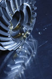 Gears, cogs, titanium and oil, lubricants. Smaller gears from aerospace industry with oil and lubricants. blue toning concept royalty free stock image