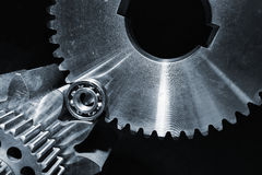 Gears and cogwheels set against black background Royalty Free Stock Photos