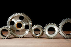 Gears from the engine. Put in a row on a black background Royalty Free Stock Images