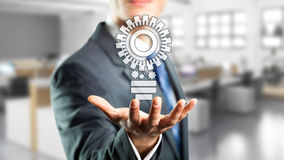 Gears forming a lightbulb and a businessman in front of an office Stock Photo