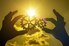 Gears in the hands of a man against a sunset sunset. stock photo