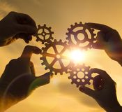 Gears in the hands of a team of people. royalty free stock photography