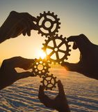 Gears in the hands of a team of people. Collection of machinery from the parts. against the background of the sunset stock images