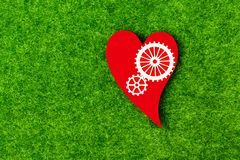 Gears, a heart of red color against the background of artificial green grass. Ecological, feelings, love stock photography
