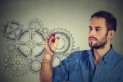 Gears and ideas creativity concept. Young man drawing gears with pen. On gray wall background Stock Photos