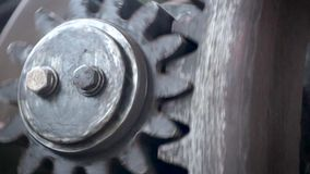 Gears of a large machine are spinning fast.
