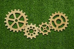 Gears of natural wood on a background of green grass symbolize green technology. Concept of ideas, cooperation, strategy, teamwork. business royalty free stock images
