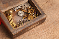 Gears and parts of the clock in the old wooden box Stock Photography