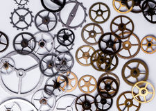 Gears on the table. Details, technology. Heap of small gears on a white background Royalty Free Stock Image