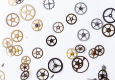 Gears on the table. Details, technology. Heap of small gears on a white background Stock Images