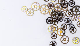 Gears on the table. Details, technology. Heap of small gears on a white background Royalty Free Stock Photo