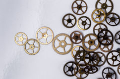 Gears on the table. Details, technology. Heap of small gears on a white background Stock Photo