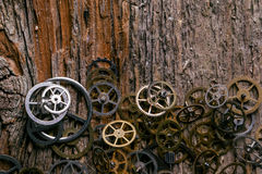 Gears on the table. Details, technology. Heap of small gears on a wooden table Royalty Free Stock Photo