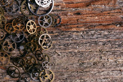 Gears on the table. Details, technology. Heap of small gears on a wooden table Stock Photography