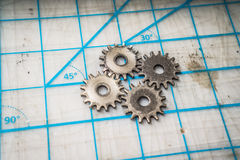 Gears on a tabletop. Four gears sit on a tabletop cutting mat Stock Photo