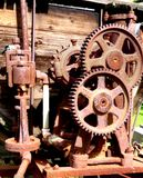 Gears in vintage sepia. Rusted and forgotten gears of an old water wagon. Interlocking gears used to drive the pump, now useless and nearly forgotten Stock Images