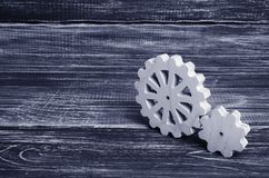 Gears of wood stand on a dark wooden background. Concept of tech. Nology and industry, engineering. Mechanical parts, technological solutions and ideas Stock Photo