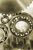 Geas, cogs and ball-bearings. Titanium and steel gears and ball-bearings, industrial engineering parts in bronze toning royalty free stock image