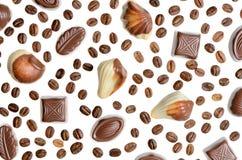 Geassorteerd chocoladesuikergoed op de achtergrond van isola van koffiebonen Stock Foto's
