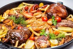 Geassorteerd vlees met aardappelplakken en gesmoorde kool In een pan stock afbeeldingen