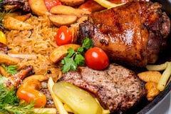 Geassorteerd vlees met aardappelplakken en gesmoorde kool In een pan stock fotografie