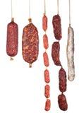 Geassorteerde die salamiworsten op witte achtergrond worden geïsoleerd Stock Foto