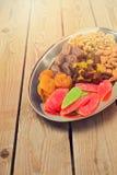 Geassorteerde droge vruchten en noten op plaat over houten achtergrond Stock Afbeeldingen