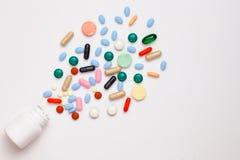 Geassorteerde farmaceutische geneeskundepillen, tabletten en capsules die uit container over witte achtergrond komen royalty-vrije stock afbeelding