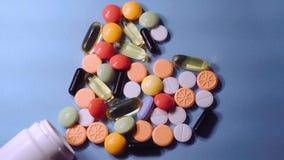 Geassorteerde farmaceutische geneeskundepillen, tabletten en capsules en fles op blauwe achtergrond stock videobeelden