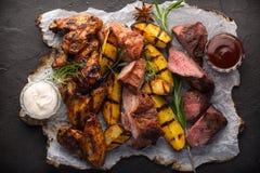 Geassorteerde geroosterde vlees en aardappels op zwarte achtergrond stock fotografie