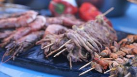 Geassorteerde heerlijke die zeevruchtendelicatessen bij het festival van het straatvoedsel voor verkoop met inbegrip van garnalen stock footage