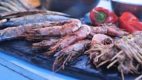 Geassorteerde heerlijke die zeevruchtendelicatessen bij het festival van het straatvoedsel voor verkoop met inbegrip van garnalen stock video