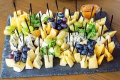 Geassorteerde Italiaanse kazen, druiven, honing en munt Het concept van eet Stock Afbeeldingen
