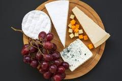 Geassorteerde kazen met druiven op ronde houten raad op donkere achtergrond Voedsel voor romantisch stock afbeeldingen