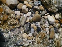Geassorteerde kleurrijke kiezelstenen op strand Stock Foto's
