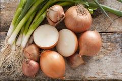 Geassorteerde landbouwbedrijf verse uien op een rustieke lijst Stock Foto's