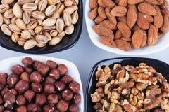 Geassorteerde noten in ceramische kommen stock afbeelding