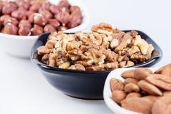 Geassorteerde noten in ceramische kommen stock fotografie