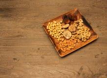 Geassorteerde noten in houten schotel Royalty-vrije Stock Afbeelding